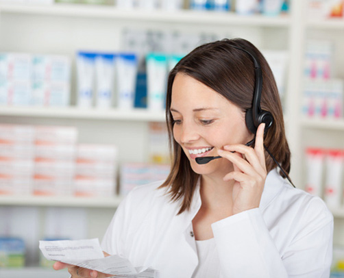 Pharmazeutisch Technische Angestellte hält ein Rezept in der Hand und spricht mit einem Kunden am Telefon